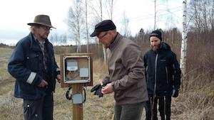 Kolme miestä asentamassa etäseurattavaa maakosteus- ja lämpötilaseurantayksikköä Koiransuolenojalle.