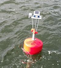 Lähikuva aurinkopaneelilla varustetusta loggerista ja signaalimuuntimesta asennettuna punaiseen poijuun merellä.