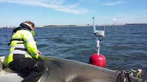 Mies asentamassa Rauman sataman sameusmittaria veneestä käsin punaiseen poijuun. Horisontissa siintää Rauman satama-aluetta.