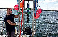 Meritutkija laivan kannella säätämässä YSI YDOC moniparametrimittausantureita merellä Storfjardenissa.