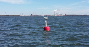 Jatkuvatoimisten sameusantureiden etäseurantalaitteet kilometrien päässä satamasta.  Punainen poiju etäseurantalaitteineen edessä ja horisontissa siintää satama-alue.