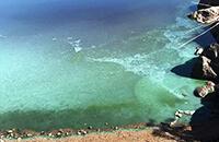 Mies lahden pohjukassa rannalla virvelöimässä. Pienellä perämoottorilla varustettu soutuvene etualalla järven rannassa. Kuva linkkinä sinileväseuranta sivulle.